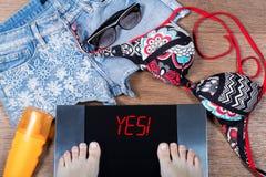 妇女在暑假前衡量自己 是词!在数字式等级 概念健康生活方式 库存照片
