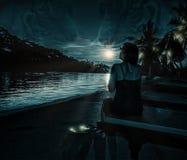 妇女在月光的晚上在海 免版税图库摄影