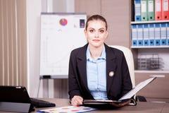 妇女在有一个图文件夹的办公室在手上 图库摄影