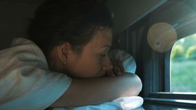 妇女在有一个开窗口的一列火车睡觉在架子顶部在一辆后备的汽车的夏天 影视素材