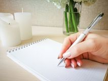 妇女在有一支美丽的笔的一个笔记本写 免版税库存图片