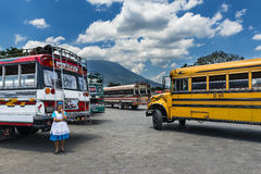 妇女在有五颜六色的公共汽车的公共汽车总站在安提瓜岛,危地马拉 图库摄影