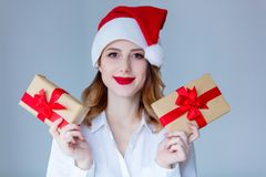 妇女在有圣诞节礼物的圣诞老人帽子 库存图片