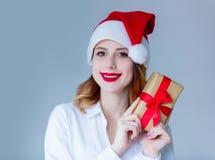 妇女在有圣诞节礼物的圣诞老人帽子 免版税库存图片