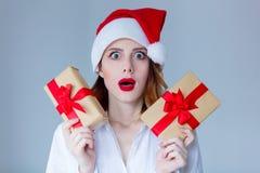 妇女在有圣诞节礼物的圣诞老人帽子 免版税库存照片
