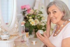 妇女在有奶油的一个卫生间里 库存照片