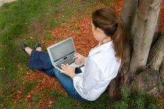 妇女在有她的计算机的公园 免版税库存图片
