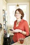 妇女在有手机的厨房里 库存照片