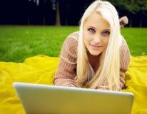 妇女在有放松的膝上型计算机的公园 免版税库存照片