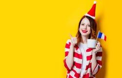 妇女在有法国旗子和杯子的圣诞老人帽子 库存图片