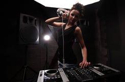 妇女在有演奏在搅拌器的白色耳机的黑人dj音乐与光束作用 在背景的大扩音器 图库摄影