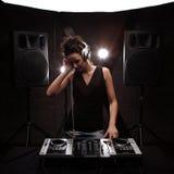 妇女在有演奏在搅拌器w的白色耳机的黑人dj音乐 库存照片