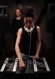 妇女在有演奏在搅拌器w的白色耳机的黑人dj音乐 免版税库存图片