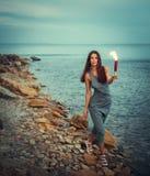 妇女在有火爱好者的海岸海洋 库存图片
