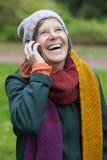 妇女在有电话的公园 免版税库存照片