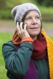 妇女在有电话的公园 免版税图库摄影