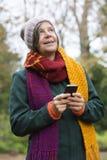 妇女在有电话的公园 库存照片