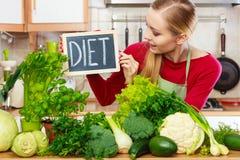 妇女在有的厨房里绿色饮食菜 免版税图库摄影