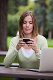 妇女在有移动电话的公园 免版税库存照片