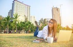 妇女在有膝上型计算机和咖啡的公园工作, 免版税库存照片