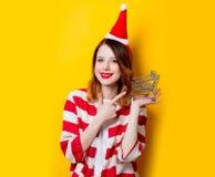 妇女在有超级市场推车的圣诞老人帽子 库存图片