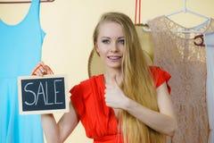 妇女在有销售标志的商店 免版税图库摄影