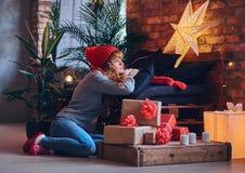 妇女在有顶楼interi的一个客厅拿着圣诞节礼物 免版税库存照片