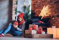 妇女在有顶楼interi的一个客厅拿着圣诞节礼物 图库摄影