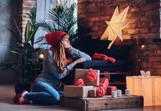 妇女在有顶楼interi的一个客厅拿着圣诞节礼物 库存图片