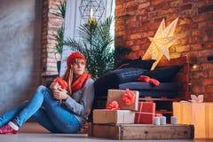 妇女在有顶楼interi的一个客厅拿着圣诞节礼物 免版税库存图片