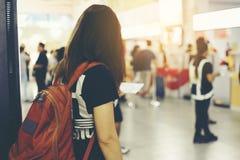 妇女在机场和票在她的手上有迷离人背景 免版税库存图片