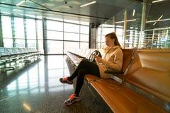 妇女在机场大厅里 等待她的飞行的妇女在机场termi 库存照片
