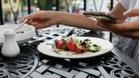 妇女在板材投入菜沙拉并且使用电话在晚餐在餐馆 影视素材
