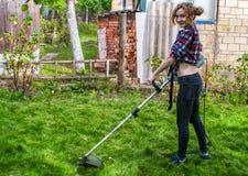 妇女在格子花呢上衣割的草坪 库存图片