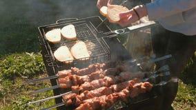 妇女在格栅机架上把面包放用葱 猪肉烤肉在串被烤在木炭格栅顶部 特写镜头 影视素材