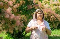 妇女在桃红色灌木背景站立  免版税图库摄影
