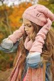 妇女在桃红色被编织的帽子,围巾穿戴了,并且手套在秋天停放 库存图片
