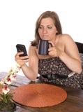 妇女在桌上坐手机 免版税图库摄影