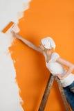 妇女在桔子的绘画墙壁 免版税库存图片