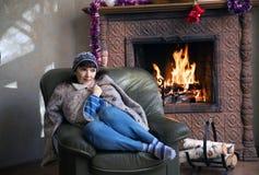 妇女在椅子坐在一个灼烧的壁炉附近 免版税库存照片