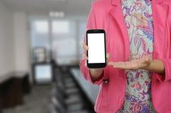 妇女在正式衣服的举行智能手机 免版税库存照片