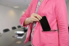 妇女在正式衣服的举行智能手机 免版税库存图片