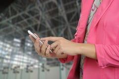 妇女在正式衣服的举行智能手机 库存照片