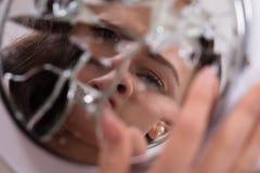 妇女在残破的镜子的` s面孔 库存照片