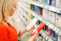 妇女在比较产品的超级市场 免版税库存照片