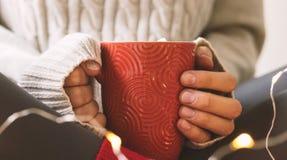 妇女在毛线衣的` s手拿着杯子热的咖啡、巧克力或者茶 概念冬天舒适,早晨喝,温暖 免版税库存照片