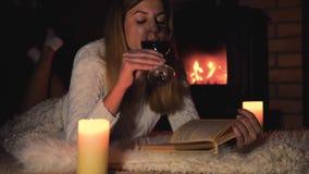 妇女在毯子说谎通过壁炉饮用的酒和读书 股票录像