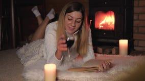 妇女在毯子说谎通过壁炉饮用的酒和读书 股票视频