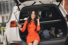 妇女在汽车的开放后车箱附近做selfie一张画象 免版税图库摄影