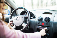 妇女在汽车的设定音乐 汽车控制台控制板电子仪器航海 无线电特写镜头 妇女设定了收音机 库存图片